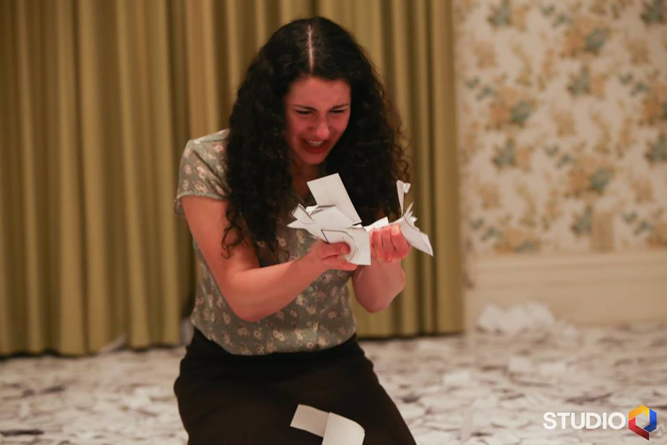 photo of a kneeling woman holding small pieces of paper