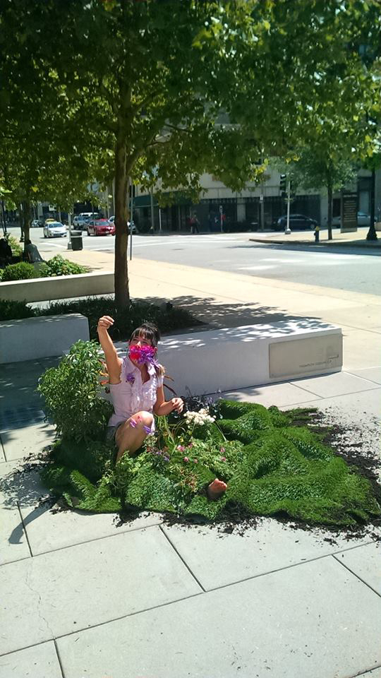 picture of a woman sitting in a sidewalk garden