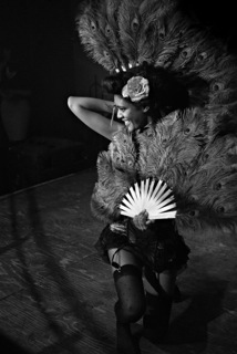 photo of a woman posing, holding a fan