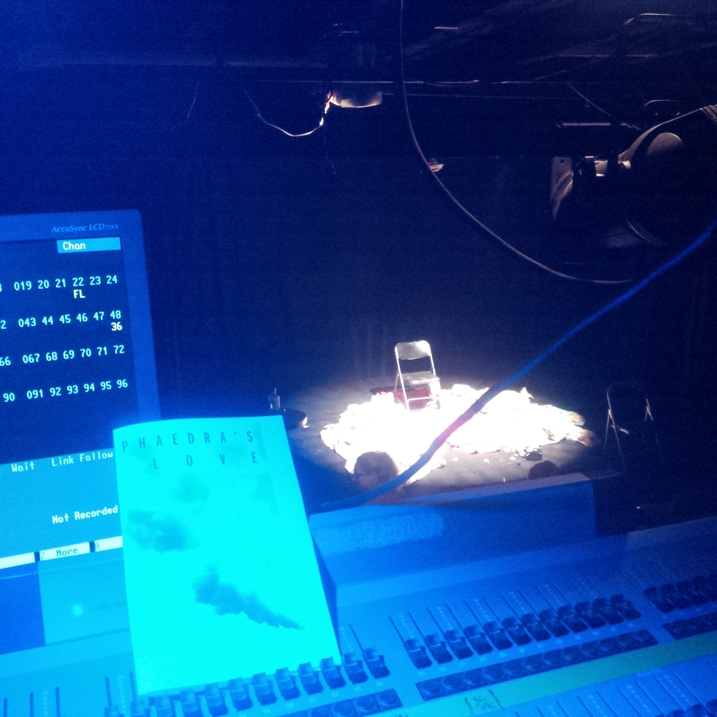 photo of a program on a sound mixing board with a spotlit chair in the background
