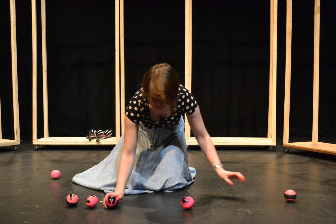 photo of a woman kneeling with small objects arranged in a semi-circle in front of her