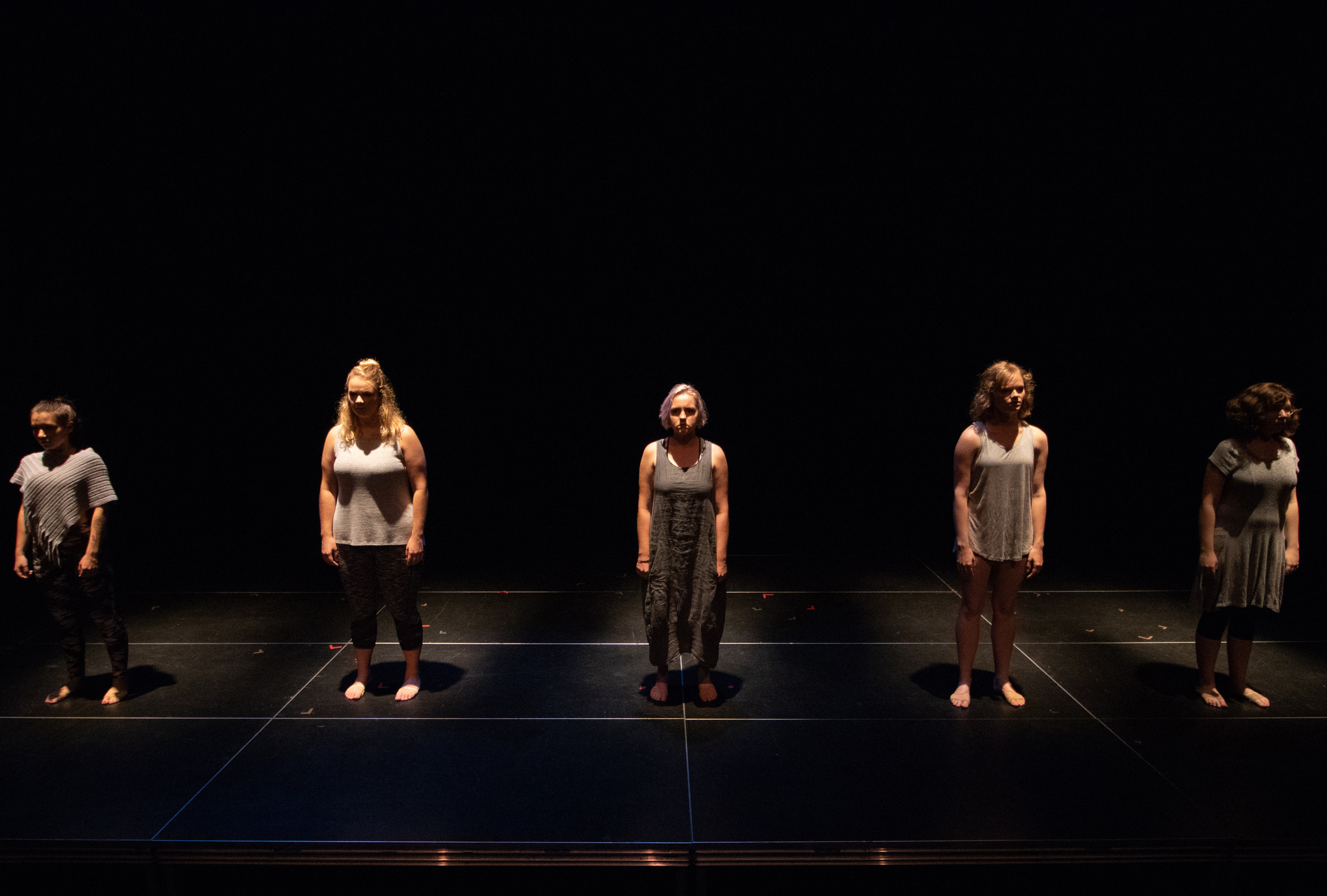 photo of five spot-lit people standing on a stage